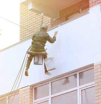 Commercial painting company Melbourne worker working on a high building while in a lift rope